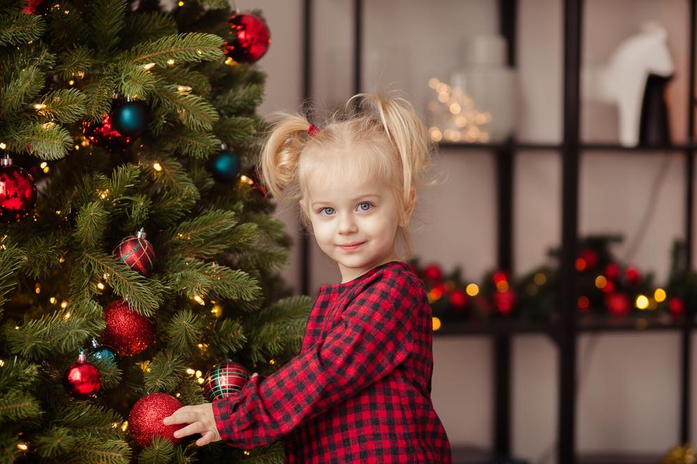 Adventszeit mit Kindern feiern, Advent in der Kita, Mädchen dekoriert Weihnachtsbaum