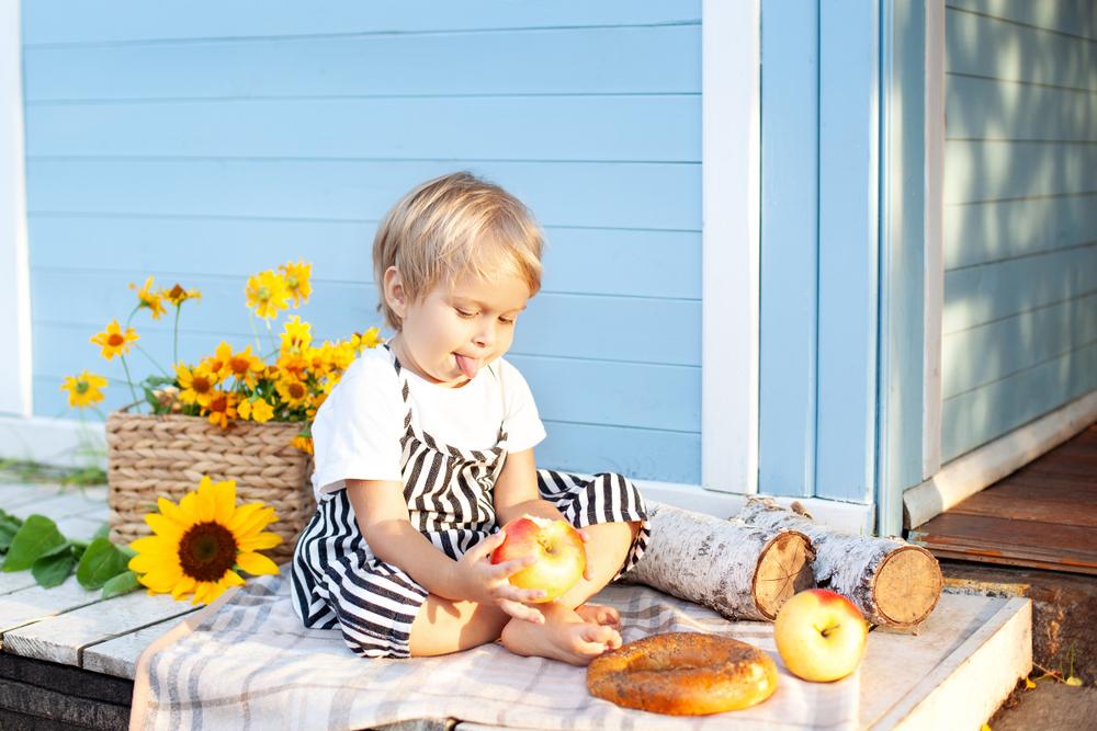 dekorieren mit Kindern im Herbst, Kind isst einen Apfel, Aktivitäten für Kinder im Kindergarten