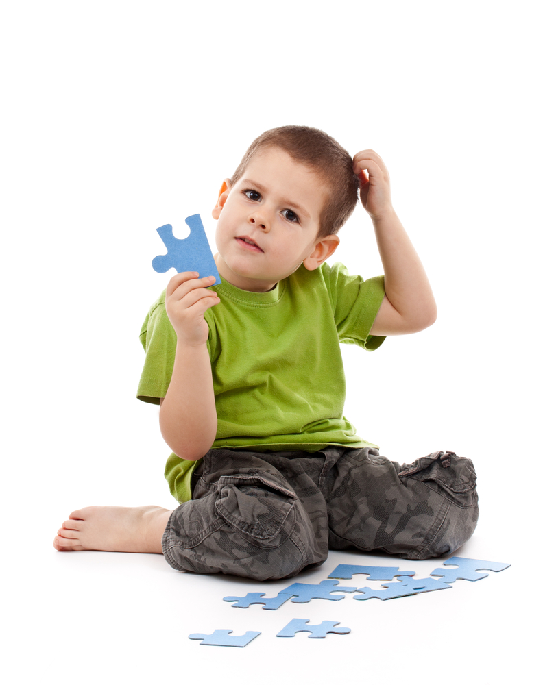 Puzzeln für mehr Konzentration bei Kindern, Junge überlegt wo das nächste Puzzleteil hingehört