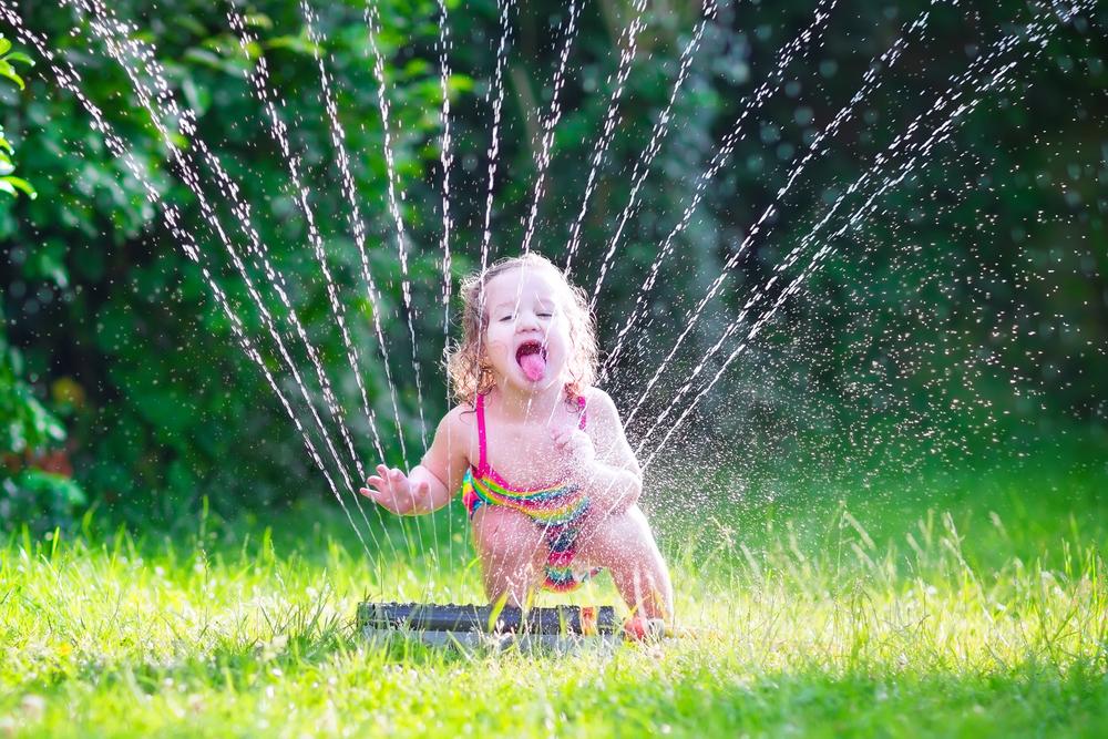 Sommer in der Kita, Kind spielt mit Wassersprenger, Sommer im Kindergarten genießen