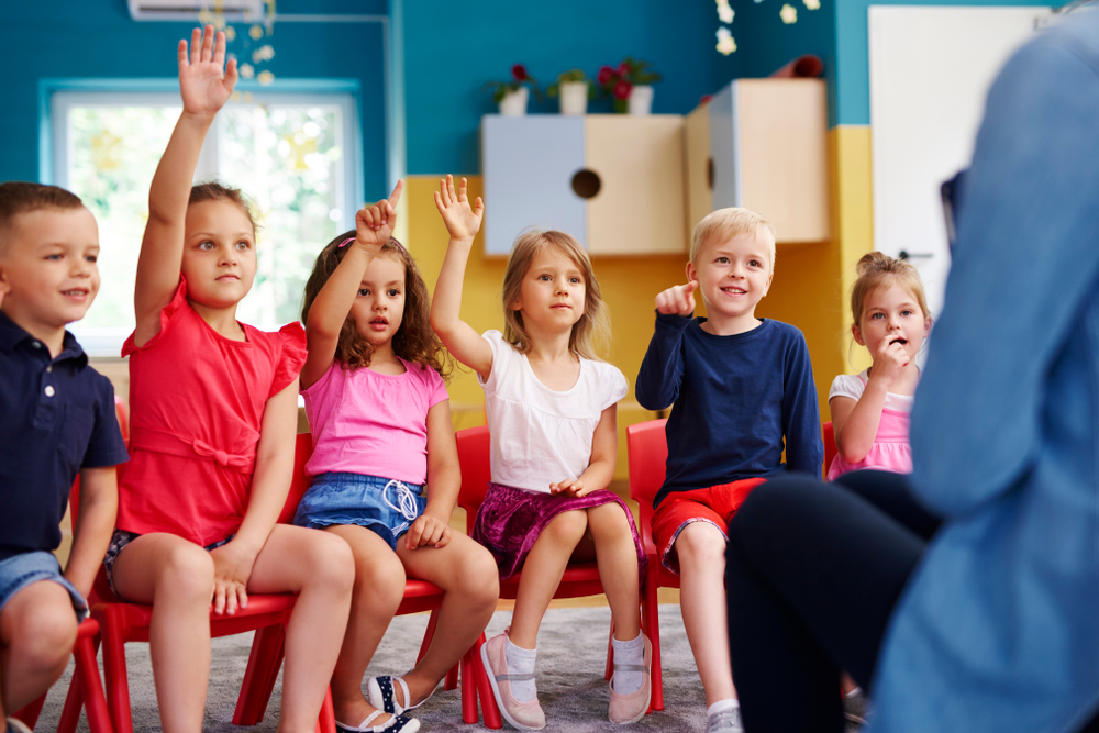 Ideen für Sommer in der Kita, Kinder sitzen im Morgenkreis, Kinder aüßern ihre Wünsche für Sommer in der Kita