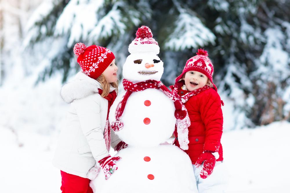 Kinder bauen einen Schneemann im Winter