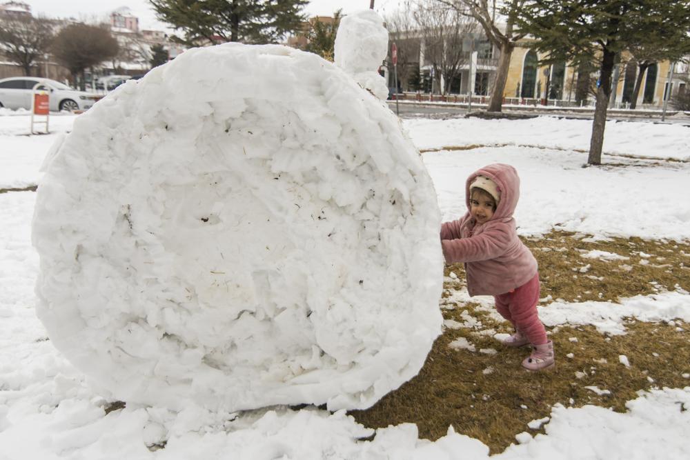 Winter in der Kita, Kind spielt mit Schnee, Kinder spielen mit einem Schneeball, Spiele im Winter für Kinder
